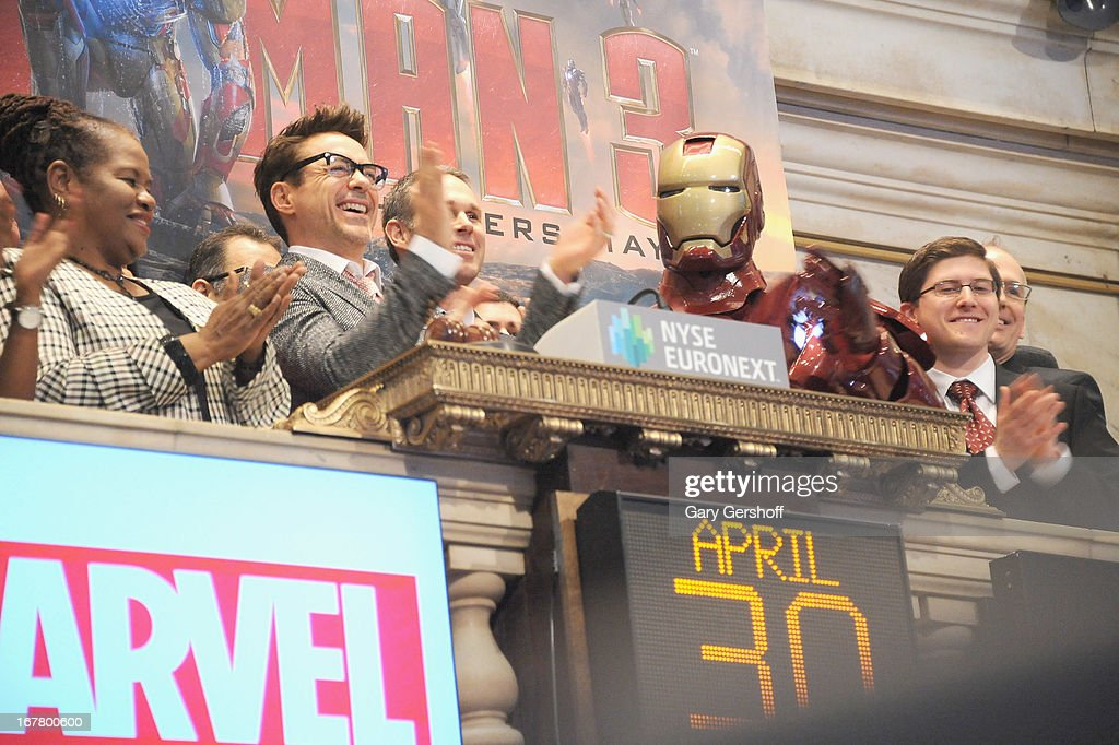 Actor Robert Downey (2nd-L) Jr.and the comic book character Iron man ring the opening bell in celebration of 'Iron Man 3' at the New York Stock Exchange on April 30, 2013 in New York City.
