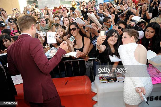 Actor Robert Pattinson and actress Kristen Stewart sign autographs as they arrive at the premiere of Summit Entertainment's 'The Twilight Saga...