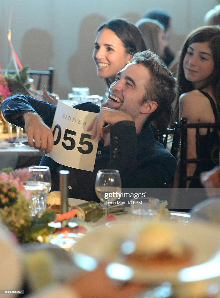 Actor <a gi-track='captionPersonalityLinkClicked' href=/galleries/search?phrase=Robert+Pattinson&family=editorial&specificpeople=734445 ng-click='$event.stopPropagation()'>Robert Pattinson</a> bids during the 6th Annual GO GO Gala at Bel Air Bay Club on November 14, 2013 in Pacific Palisades, California.