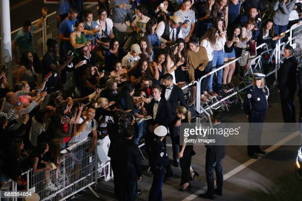 Actor Robert Pattinson greets fans as he arrives at the 'Good Time' screening during the 70th annual Cannes Film Festival at Palais des Festivals on...