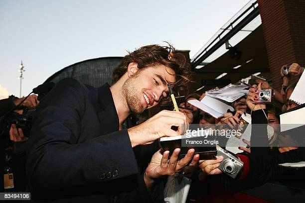 Actor Robert Pattinson signs autographs for the fans while attending the 'Twilight' Premiere during the 3rd Rome International Film Festival held at...