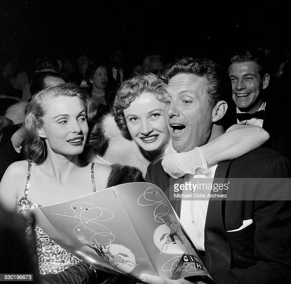 Actor Robert Stack and Rosemarie Bowe are surprised by Carol Ohmart before a premiere in Los AngelesCA
