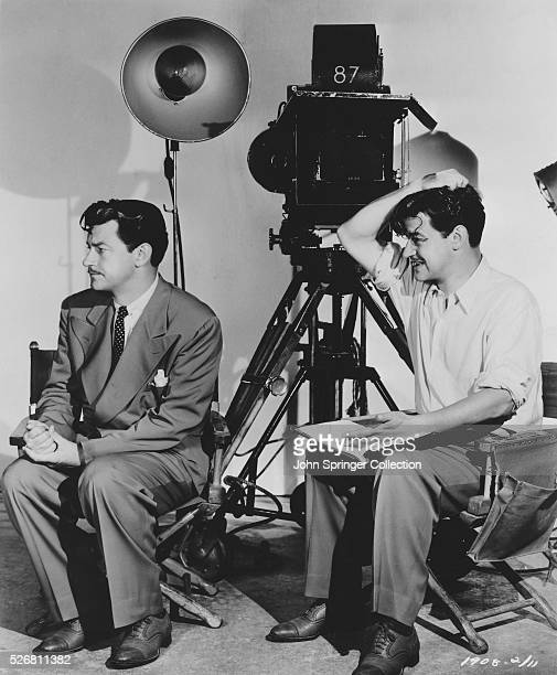 Actor Robert Taylor and director Preston Sturges Seated near Cameras