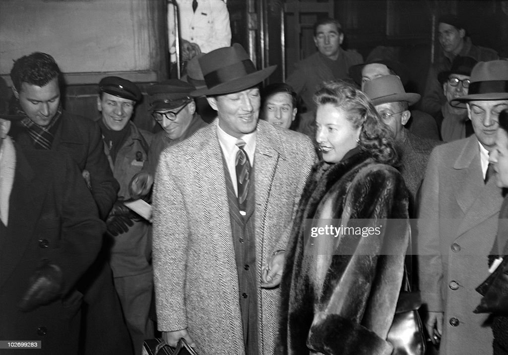 US actor Robert Taylor (C) and his wife, US actress <a gi-track='captionPersonalityLinkClicked' href=/galleries/search?phrase=Barbara+Stanwyck&family=editorial&specificpeople=90352 ng-click='$event.stopPropagation()'>Barbara Stanwyck</a> (2nd R), arrive from London at the Gare du Nord station in Paris, 20 February 1947. In 1947, Taylor testified before the HUAC (House Un-American Activities Committee) during the anti-Communist witchhunt instigated by John Parnell Thomas which generated denunciations in the movie industry, and the condemnation of the Hollywood 10.