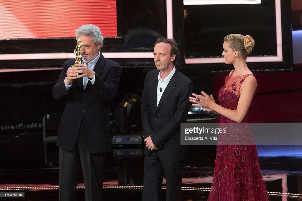 Actor Roberto Benigni (C) and composer Nicola Piovani (L) appear on stage during the 2013 Premi David di Donatello Ceremony Awards at Dear RAI Studios on June 14, 2013 in Rome, Italy.