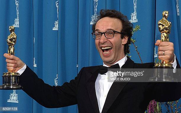 Actor Roberto Benigni of Italy holds his two Oscars for Best Foreign Language Film and Best Actor for 'Life is Beautiful' at the 71st Annual Academy...
