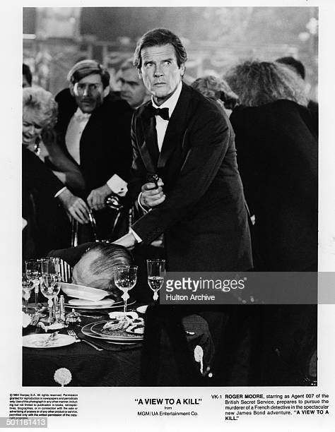 Actor Roger Moore as James Bond 007 holds a gun in a scene from the MGM/UA movie 'A View to a Kill' circa 1984