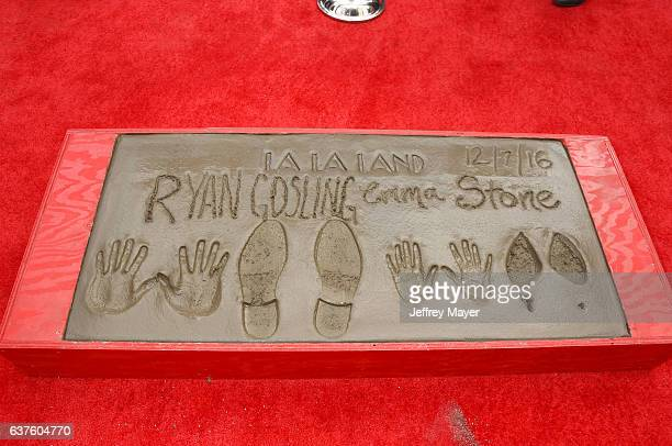 Actor Ryan Gosling and actress Emma Stone hands and feet in cement at the Hand And Footprint Ceremony for Ryan Gosling and Emma Stone at the TCL...