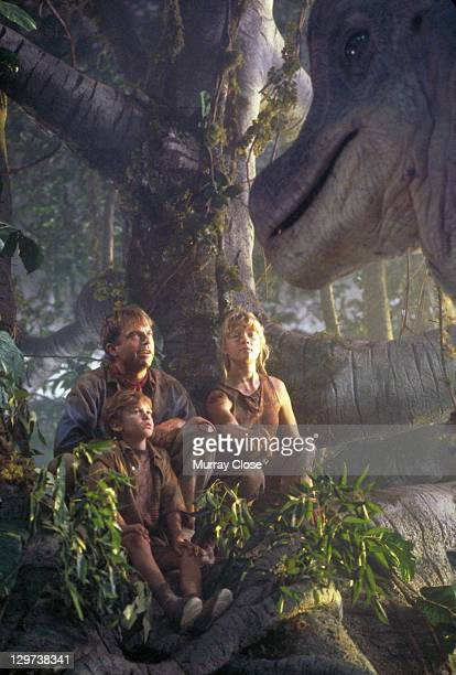 Actor Sam Neill as Dr Alan Grant with Ariana Richards and Joseph Mazzello as Lex and Tim approached by a curious Brachiosaurus in a scene from the...
