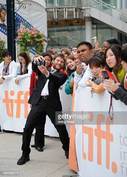 Actor Sam Worthington takes a photo with fans as he attends 'Last Night' Premiere during the 35th Toronto International Film Festival at Roy Thomson...