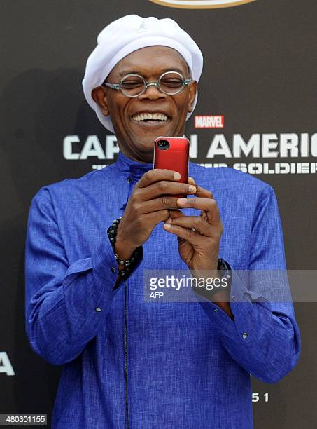 US actor Samuel L Jackson takes a picture with his cellphone as he arrives to attend a press conference of the film Captain America The Winter...