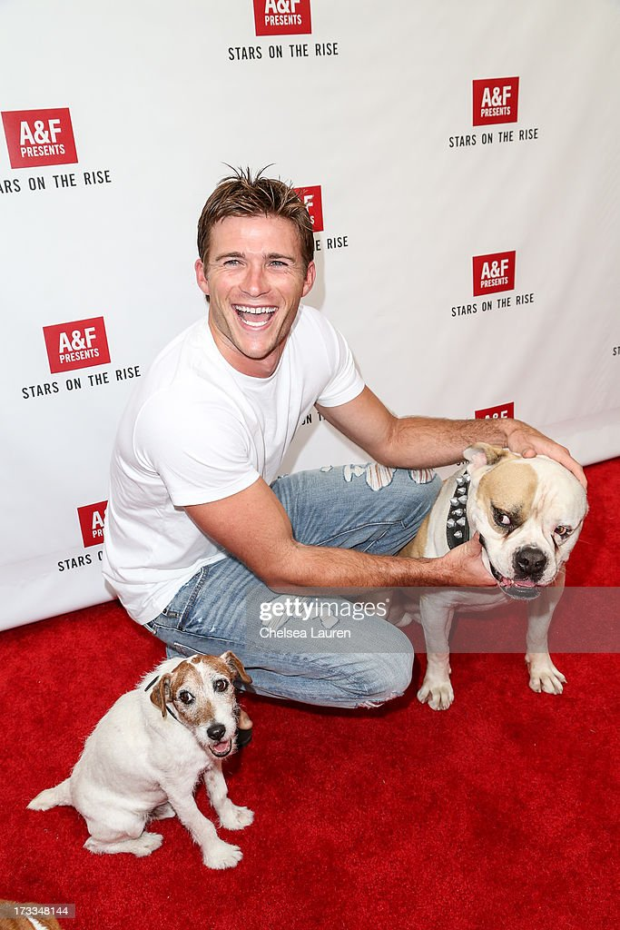 Actor Scott Eastwood and actor dogs Popeye(R) and Uggie attend Abercrombie & Fitch's 'Stars on the Rise' event at Abercrombie & Fitch on July 11, 2013 in Los Angeles, California.