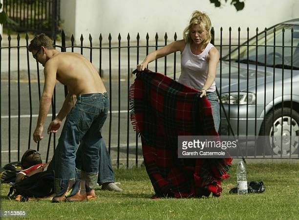 Actor Scott Maslen and actress Samantha Janus enjoy the sun together on Primrose Hill July 11 2003 in North London England