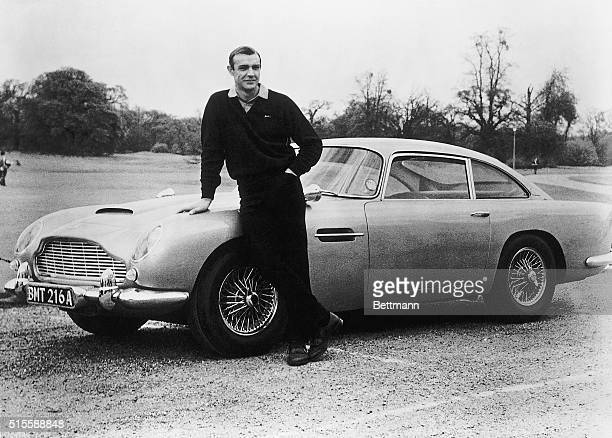 Actor Sean Connery the original James Bond is pictured here on the set of Goldfinger with one of the fictional spy's cars a 1964 Aston Martin DB5