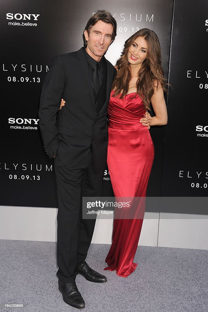 Actor Sharlto Copley and model Tanit Phoenix arrive at the Los Angeles premiere of 'Elysium' at Regency Village Theatre on August 7, 2013 in Westwood, California.