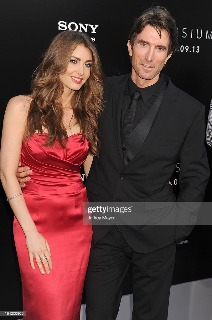 Actor Sharlto Copley (R) and model Tanit Phoenix arrive at the Los Angeles premiere of 'Elysium' at Regency Village Theatre on August 7, 2013 in Westwood, California.