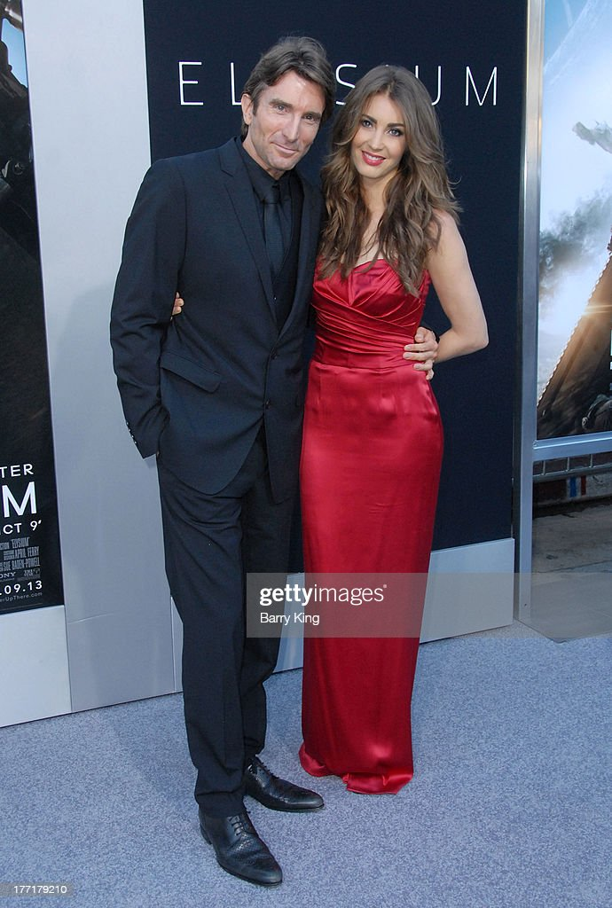 Actor Sharlto Copley (L) and Tanit Phoenix arrive at the Los Angeles Premiere of 'Elysium' on August 7, 2013 at Regency Village Theatre in Westwood, California.