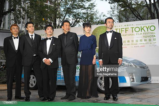 Actor Shun Oguri director Shuichi Okita actor Koji Yakusho and Asami Usuda pose on the green carpet during the Tokyo International Film Festival...
