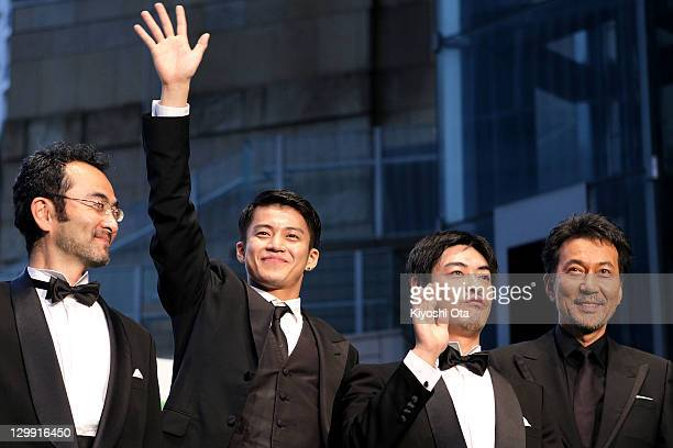 Actor Shun Oguri waves to fans next to actor Kanji Furutachi director Shuichi Okita and actor Koji Yakusho during the 24th Tokyo International Film...