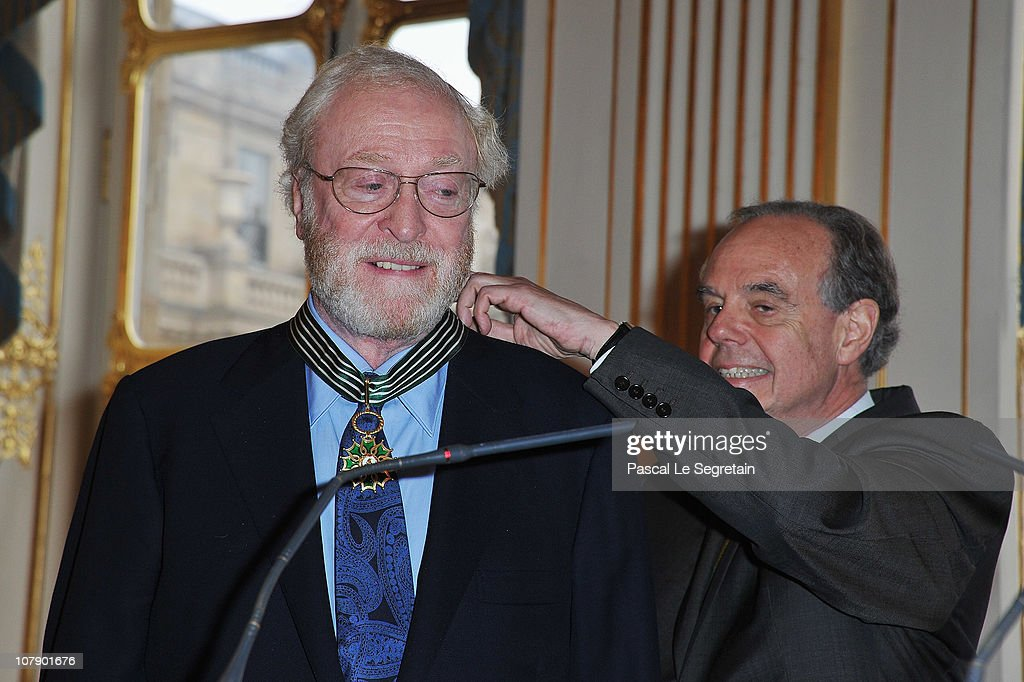 Actor Sir <a gi-track='captionPersonalityLinkClicked' href=/galleries/search?phrase=Michael+Caine+-+Actor&family=editorial&specificpeople=159746 ng-click='$event.stopPropagation()'>Michael Caine</a> (L) smiles as he is awarded 'Commandeur des arts et des lettres' by French Culture Minister <a gi-track='captionPersonalityLinkClicked' href=/galleries/search?phrase=Frederic+Mitterrand&family=editorial&specificpeople=621709 ng-click='$event.stopPropagation()'>Frederic Mitterrand</a> (R) at Ministere de la Culture on January 6, 2011 in Paris, France.