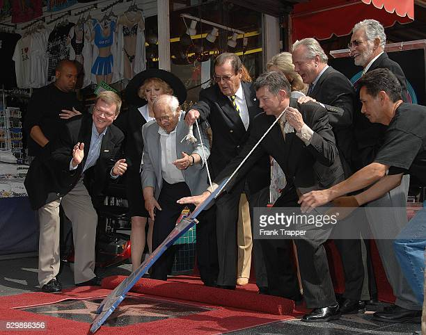 Actor Sir Roger Moore with Johnny Grant and actor David Hedison at the star ceremony honoring Moore on the Hollywood Walk of Fame