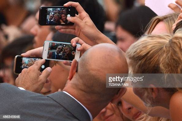 US actor Stanley Tucci poses with fans as he arrives for the screening of the movie 'Spotlight' presented out of competition at the 72nd Venice...