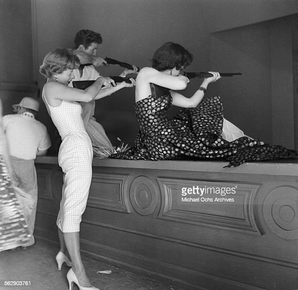 Actor Steve Rowland and actress Kathleen Case and Adelle August pose as they play arcade games during the Opening day of Disneyland in...