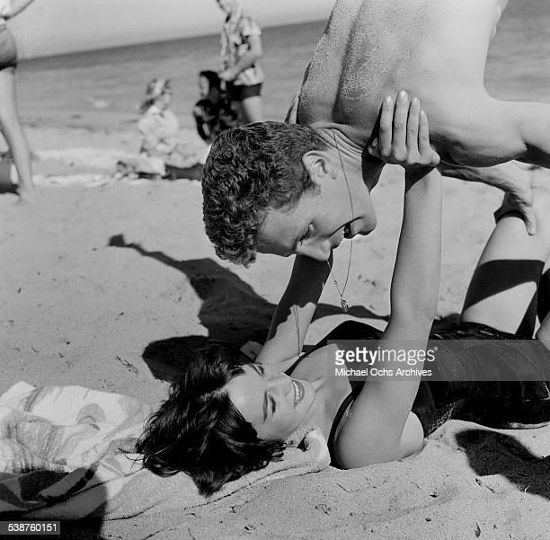 Actor Steve Rowland balances on actress Natalie Wood during the Thalians Beach Ball in MalibuCalifornia