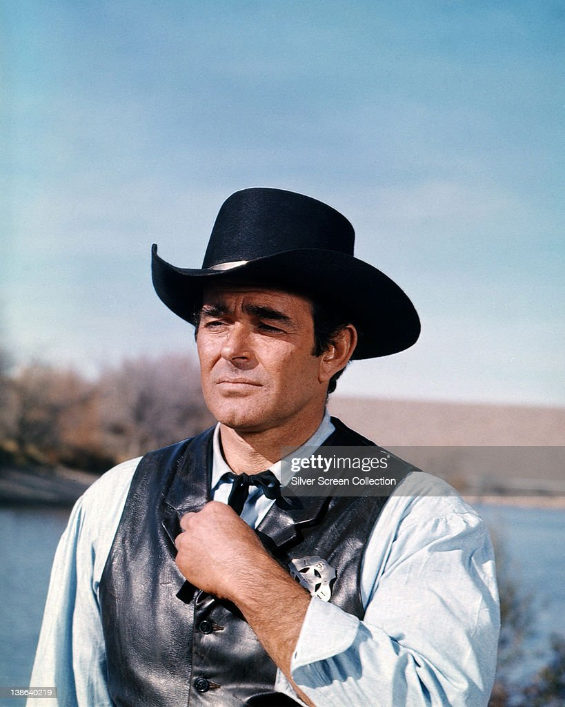 US actor Stuart Whitman wearing a black Western hat and black leather waistcoat with a sheriff's badge in a scene from the American western television series 'Cimarron Strip', USA, circa 1967.
