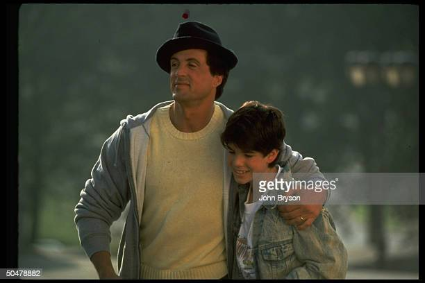Actor Sylvester Stallone w arm around son Sage in scene fr motion picture Rocky V