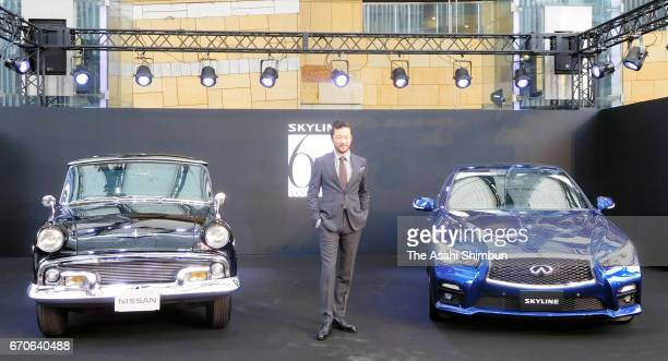 Actor Tadanobu Asano poses for photographs with Nissan Motor Co's 'Skyline' first edition 'ALSI1' and latest edition '350T Hybrid Type SP 60th...
