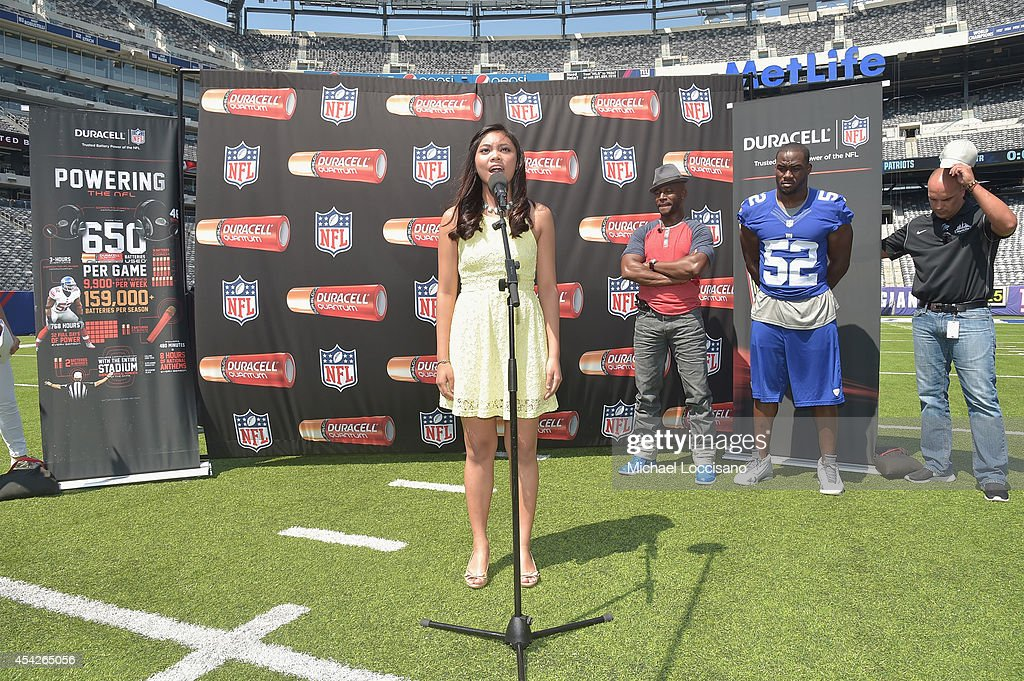 Actor Taye Diggs (C) and professional football player Jon Beason (R) look on as singer Lianah Sta Ana sings the national anthem during an interactive tour of MetLife Stadium on August 27, 2014 in East Rutherford, New Jersey.