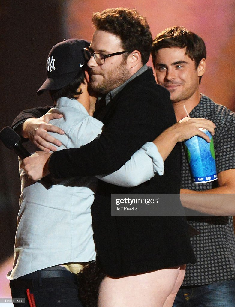 Actor Taylor Lautner accepts an award from actors Seth Rogen and Zac Efron onstage during the 2013 MTV Movie Awards at Sony Pictures Studios on April 14, 2013 in Culver City, California.