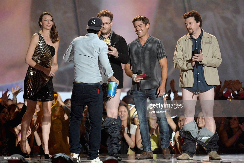 Actor Taylor Lautner accepts an award from actors Seth Rogen, Zac Efron, and Danny McBride onstage during the 2013 MTV Movie Awards at Sony Pictures Studios on April 14, 2013 in Culver City, California.