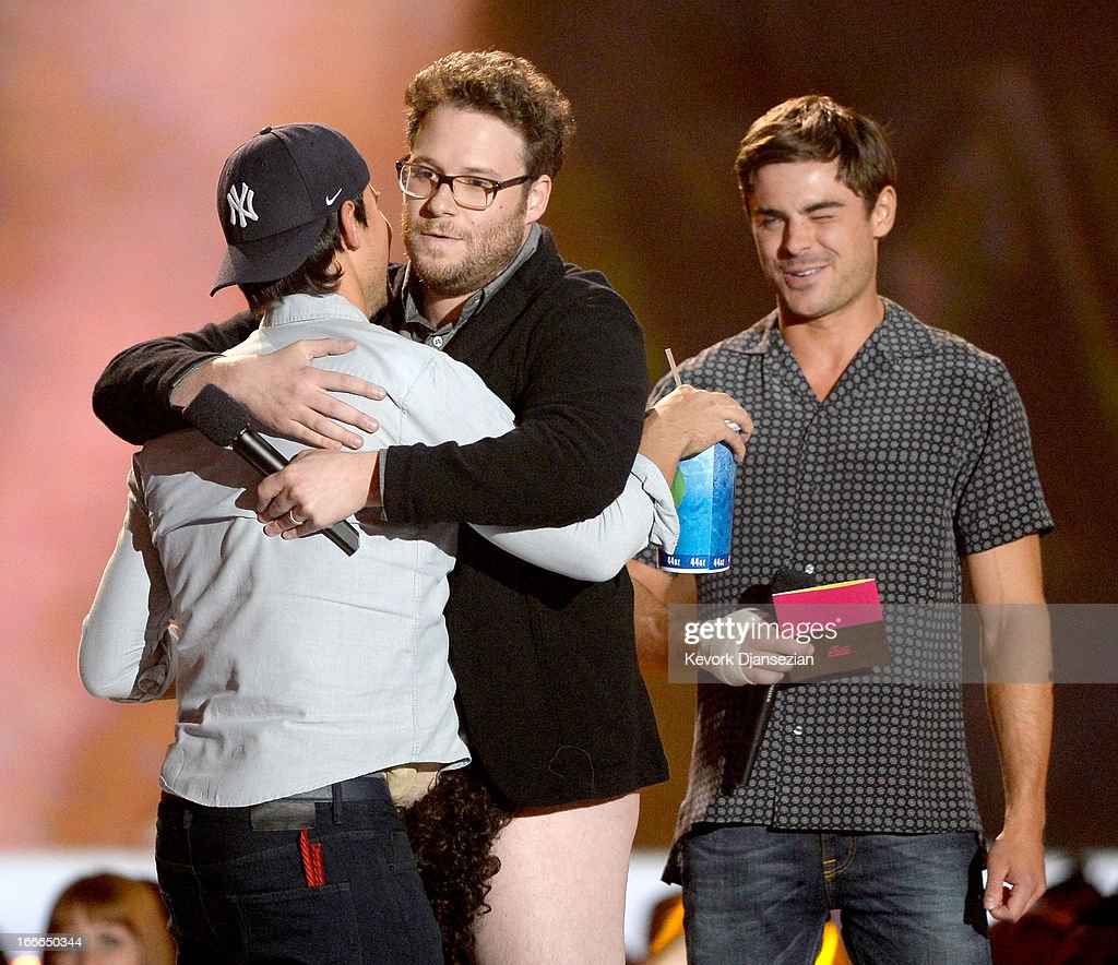 Actor Taylor Lautner accepts Best Shirtless Performance award from actors Seth Rogen and Zac Efron onstage during the 2013 MTV Movie Awards at Sony Pictures Studios on April 14, 2013 in Culver City, California.
