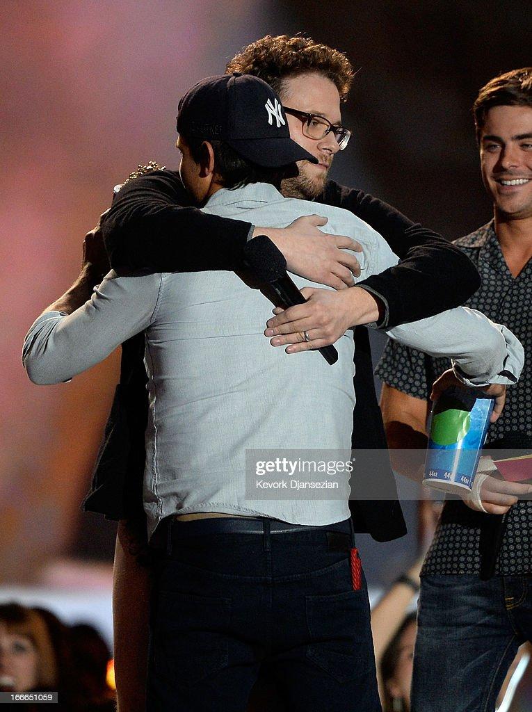 Actor Taylor Lautner (L) accepts the Best Shirtless Actor award from Seth Rogen onstage during the 2013 MTV Movie Awards at Sony Pictures Studios on April 14, 2013 in Culver City, California.