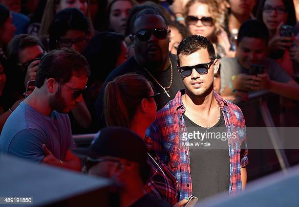 Actor Taylor Lautner stands in a crowd at The Daytime Village during the 2015 iHeartRadio Music Festival at the Las Vegas Village on September 19...
