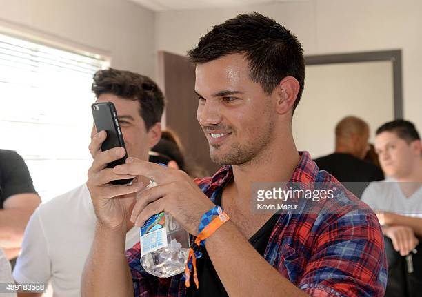 Actor Taylor Lautner takes a smartphone photo at The Daytime Village during the 2015 iHeartRadio Music Festival at the Las Vegas Village on September...