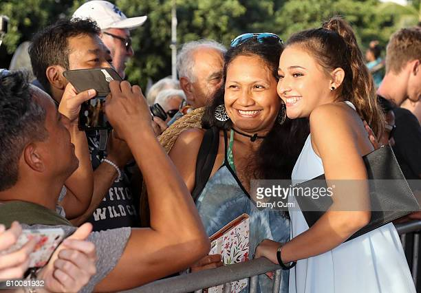 Actor Teilor Grubbs poses for a photo with a fan as she arrives at the CBS 'Hawaii Five0' Sunset On The Beach Season 7 Premier Event at Queen's Surf...
