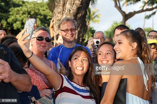 Actor Teilor Grubbs poses for a selfie with two fans as she arrives at the CBS 'Hawaii Five0' Sunset On The Beach Season 7 Premier Event at Queen's...