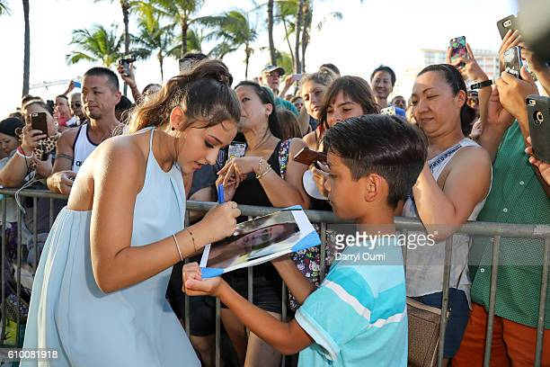 Actor Teilor Grubbs signs an autograph for a fan as she arrives at the CBS 'Hawaii Five0' Sunset On The Beach Season 7 Premier Event at Queen's Surf...
