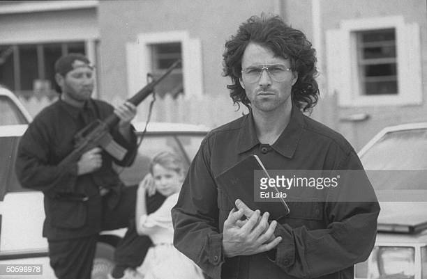 Actor Tim Daly holds a bible as he stands outside the set of the compound near an armed male who stands guard with a female companion by car in...