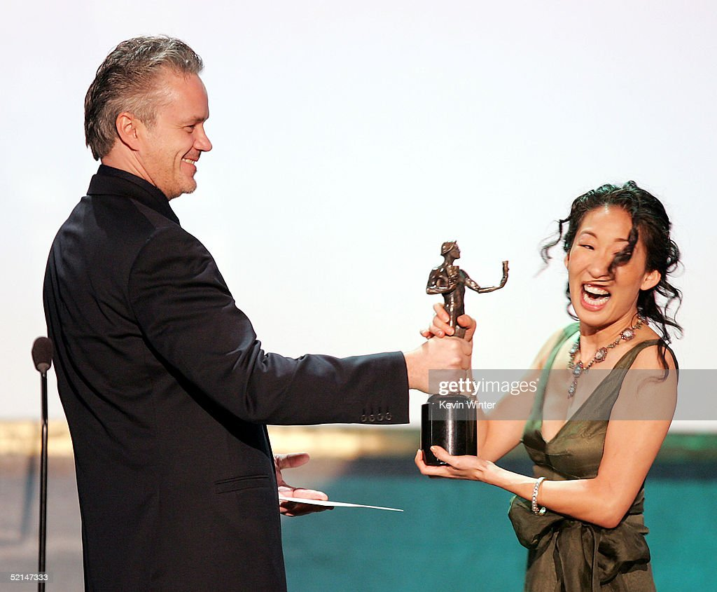 Actor Tim Robbins presents Oustanding Cast in a Motion Picture for 'Sideways' to actress Sandra Oh at the 11th Annual Screen Actors Guild Awards show at the Shrine Auditorium on February 5, 2005 in Los Angeles, California.