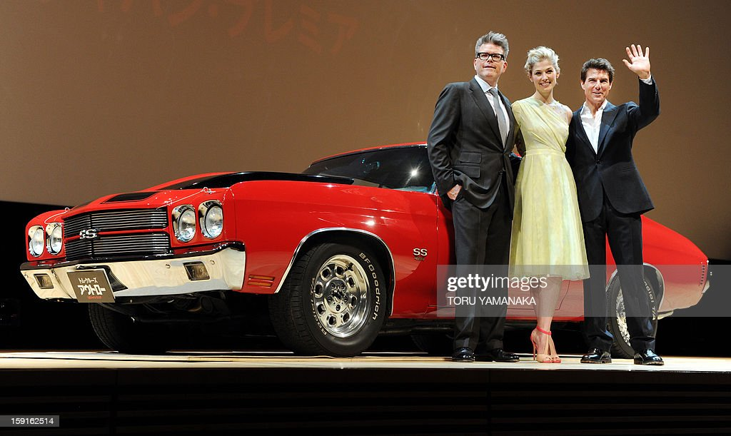 US actor Tom Cruise (R), actress Rosamund Pike (C) and director Christopher McQuarrie (L) stand beside a Chevrolet Chevelle SS, which is the same model used in their latest film, before the Japan Premiere of their latest movie, 'Jack Reacher' in Tokyo on January 9, 2013. The film will be shown nation wide from Feburary 1. AFP PHOTO/Toru YAMANAKA