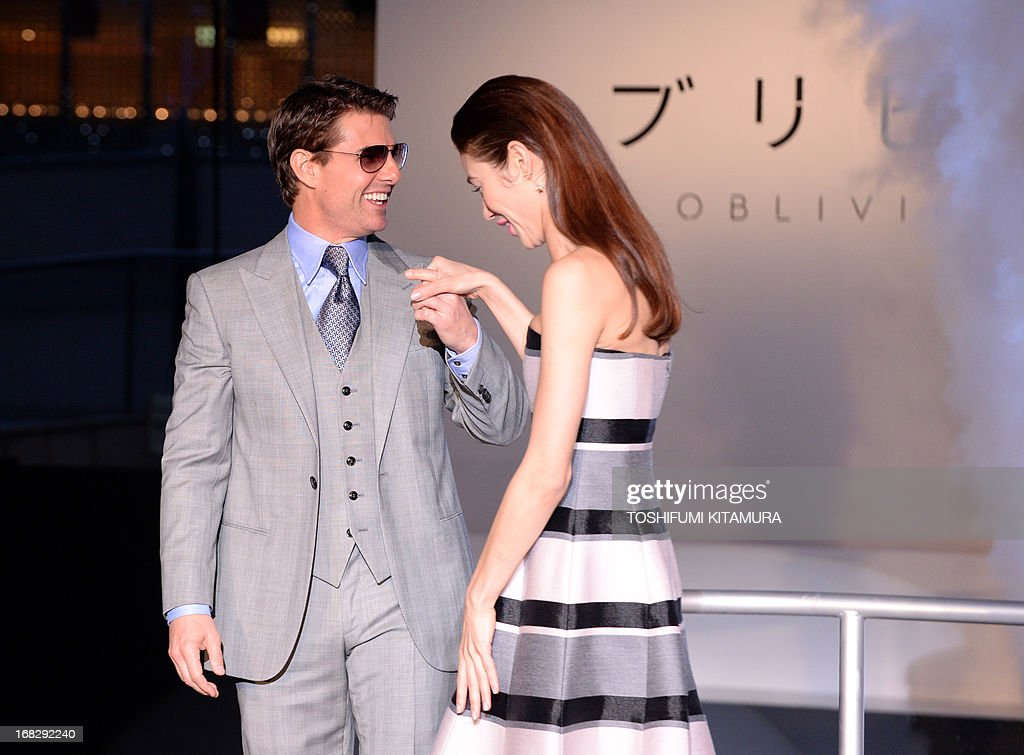 US actor Tom Cruise (L) escorts Ukraine-born French actress Olga Kurylenko (R) during their latest movie 'Oblivion' Japan premier in Tokyo on May 8, 2013. The science fiction movie, produced and directed by US film director Joseph Kosinski, will be released in Japan from May 31.