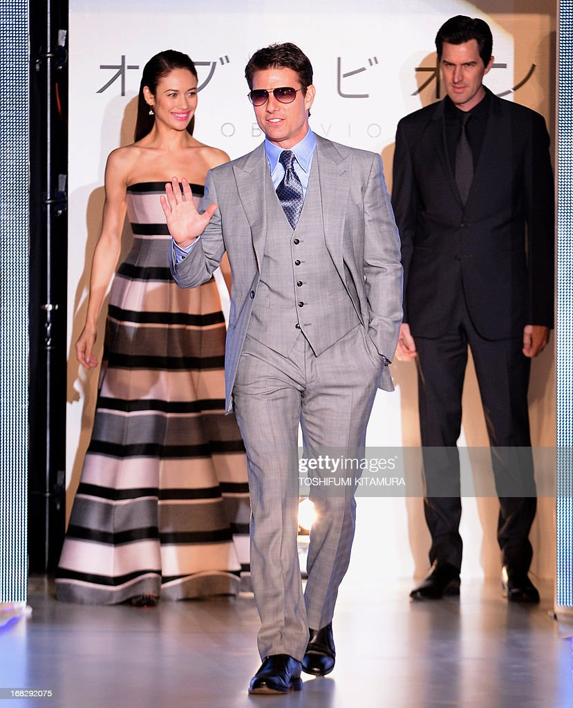 US actor Tom Cruise (C) greets his fans during his latest movie 'Oblivion' Japan premier with Ukraine-born French actress Olga Kurylenko (L) and US film director Joseph Kosinski (R) in Tokyo on May 8, 2013. The science fiction movie, produced and directed by Kosinski, will be released in Japan from May 31.