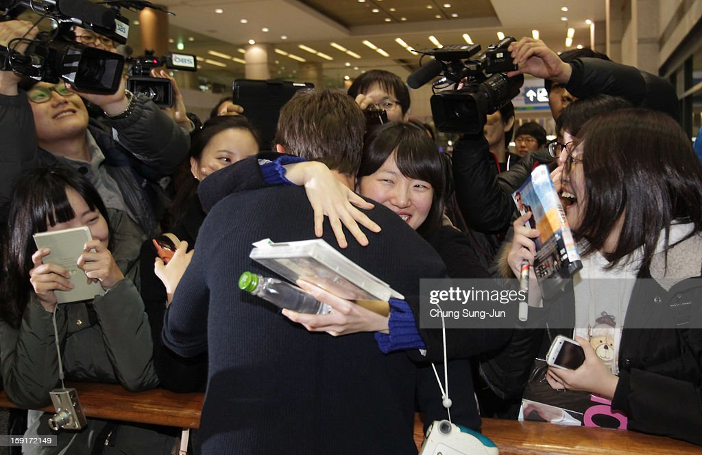 Actor Tom Cruise (C) is embraced by a fan as he arrives at Incheon International Airport on January 9, 2013 in Incheon, South Korea.