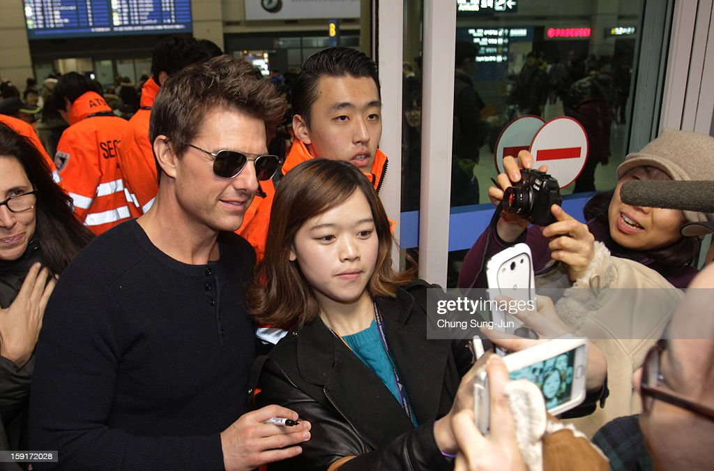 Actor Tom Cruise poses with fans as he arrives at Incheon International Airport on January 9, 2013 in Incheon, South Korea.