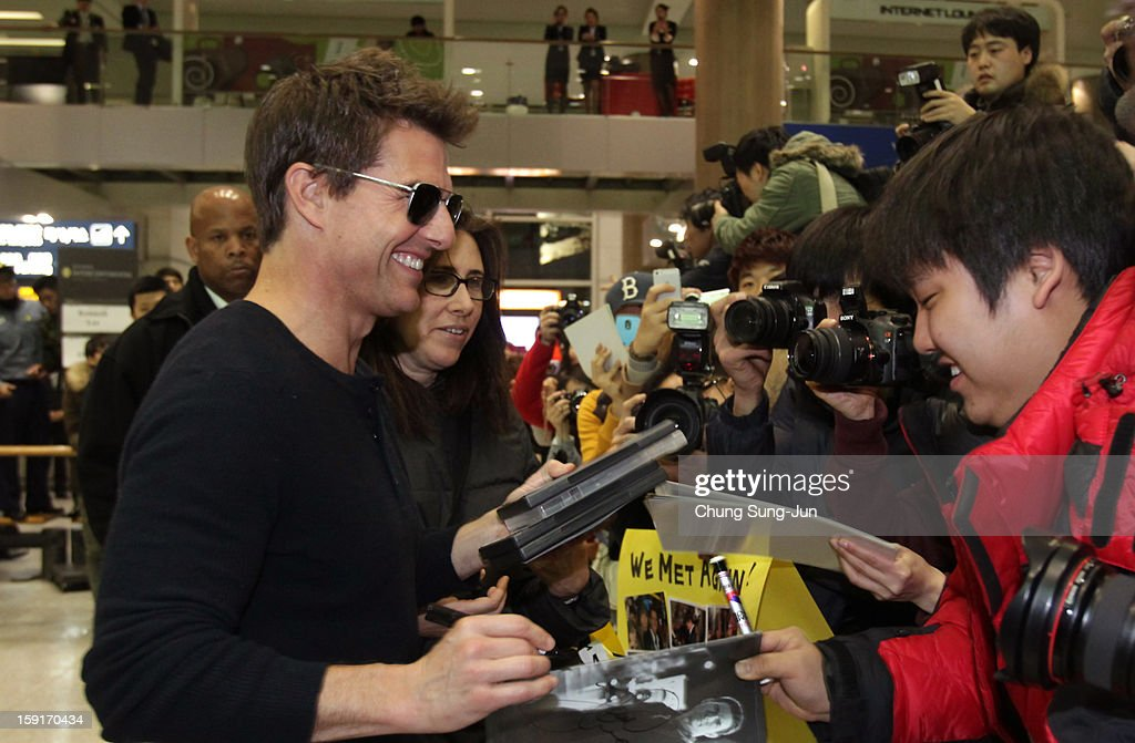 Actor Tom Cruise signs autographs for fans as he arrives at Incheon International Airport on January 9, 2013 in Incheon, South Korea.