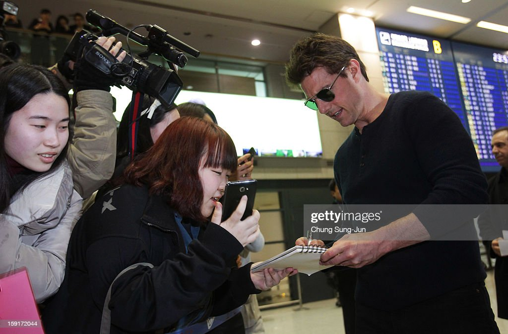 Actor <a gi-track='captionPersonalityLinkClicked' href=/galleries/search?phrase=Tom+Cruise&family=editorial&specificpeople=156405 ng-click='$event.stopPropagation()'>Tom Cruise</a> signs autographs for fans as he arrives at Incheon International Airport on January 9, 2013 in Incheon, South Korea.